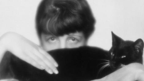 "Peeking out shyly, but formidably, from behind a black cat, in a self-portrait from 1929, Dora Kallmus – ""Fraulein D'Ora"".jpg"